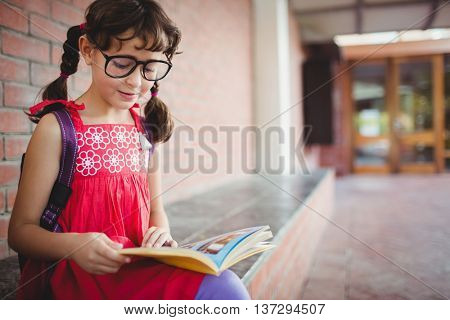 Seated schoolgirl reading a book during a break