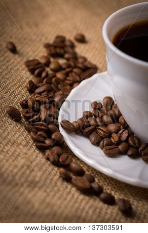 White cup of coffee with saucer and coffeebeans on linen material closeup cutted.