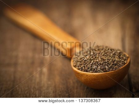 Closeup of ajwain seeds in a wooden spoon