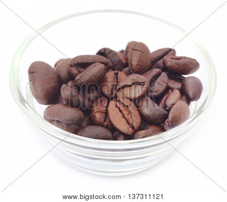 Roasted coffee bean in a glass bowl over white background