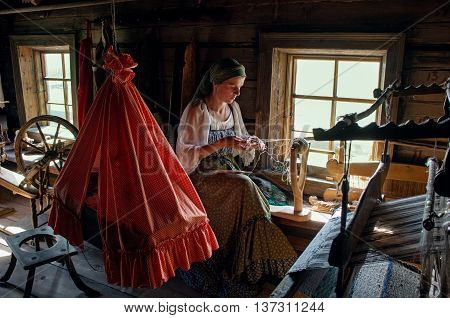 KIZHI RUSSIA - AUG 07 2015: Women in traditional russian costume weaves in Historico-architectural museum Kizhi on Kizhi island Karelia Russia.
