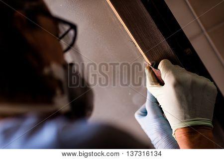 Person In Gloves Sanding Frame Around Door