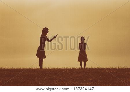Silhouette of a angry mother scolding her daughter.