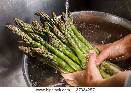 Man's hands washing asparagus. Asparagus under flow of water. Greenery bought at farmer's market. Food high on vitamins.