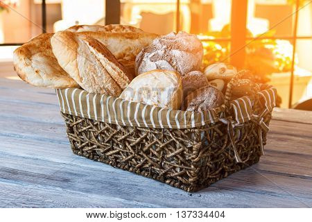 Basket with bread. Bread basket on wooden table. Morning in bakery. Choose your favorite sort.