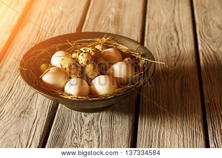 Bowl with eggs and straw. Whole eggs on hay. Product rich in protein. Fresh eggs from farmer's market.