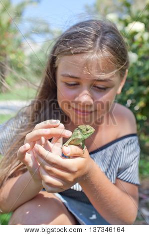 Gaily trapped chameleon and cute little girl