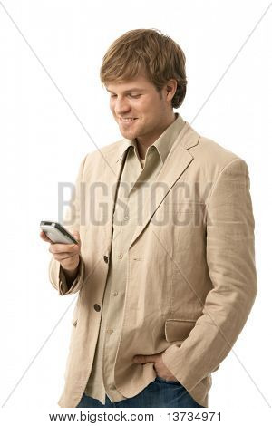 Young man writing text message on smart phone, looking at screen, smiling. Isolated  on white.?