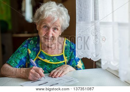 An elderly woman fills out forms utilities sitting at table in house.