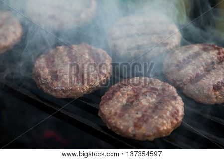 Burgers are fried on the heated grill lattice