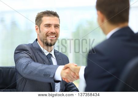 Two successful businessman sitting at the table and shaking hands