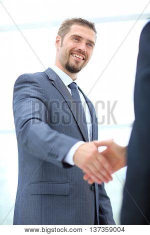 Businessman handshaking colleague in an office