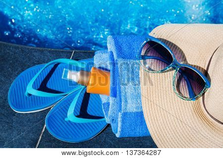 Slippers, Sunsscreen Cream, Hat, Sunglasses Near Swimming Pool Holiday Concept