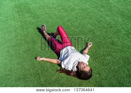 Tired athlete lying down from heat exhaustion on grass park after intense workout. Exhausted Asian runner woman taking a break sweating during cardio running exercise training in summer outdoors.