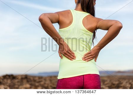 Trail running runner with painful lower back pain injury or strained muscle near the spine. Female athlete from behind on outdoor run pressing body with hands for muscles cramping soreness.
