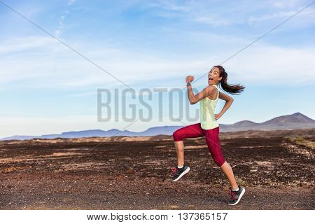 Funny runner athlete goofy woman having fun jogging on outdoor mountain nature trail. Running fitness motivation trainer or friend playful to help having energy while exercising cardio workout.