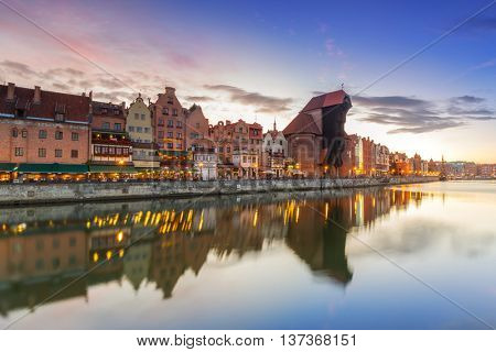 GDANSK, POLAND - 21 JUNE 2016: Medieval port crane over Motlawa river at night. This port crane built between 1442 and 1444 is the symbol of Gdansk and the oldest surviving port crane in Europe.