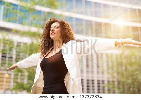 Woman opening her arms and relaxing. Lens flare effect