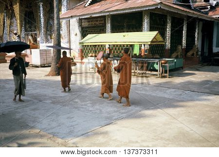 RANGOON / MYANMAR - CIRCA 1987: Three Buddhist monks in saffron robes walk through the Shwedagon Pagoda in Rangoon.