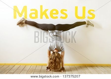 Fit woman doing a handstand near the wall below the phrase