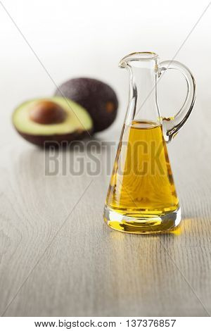 Bottle of avocado oil and fresh avocado in the background
