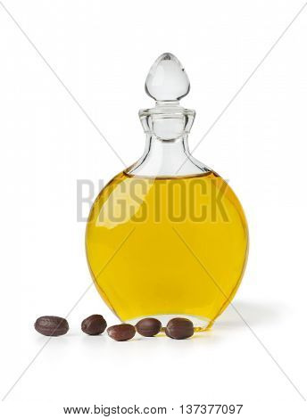 Bottle of Jojoba oil and seeds on white background