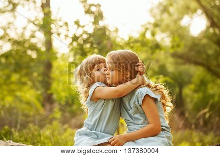 Two cute little sisters hugging in a park on a sunny summer day. Younger sister kissing elder. Family time.