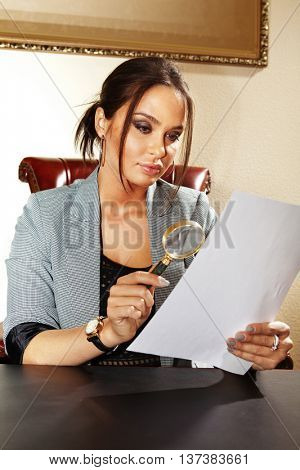 business woman looks on one document by magnifying glass