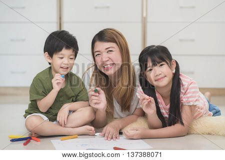 Close up Asian family drawing picture with crayons
