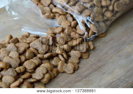 dog food pour from plastic bag on wooden plank