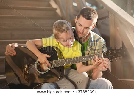 father learning his boy to play guitar, they sit on the steps of a country house on a warm summer evening.