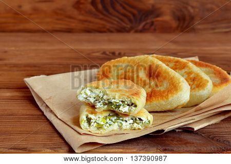 Fried pies with homemade cottage cheese, green onion and dill on paper and wooden background. Yeast-free pies recipe. A rustic style. Close-up