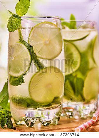 Alcohol drink. On wooden boards two glasses alcohol drink and ice cubes. A drink number forty one cocktail mohito with straw and lime and mint leaf. Country life. Outdoor. Light background.