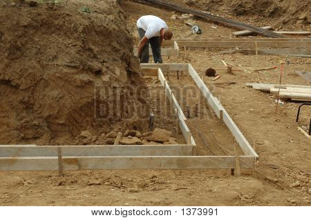 Construction Worker Laing Down Foundation