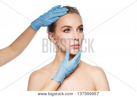 people, cosmetology, plastic surgery and beauty concept - surgeon or beautician hands touching woman face over white background