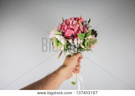 male hand giving wedding bouquet, first-person view