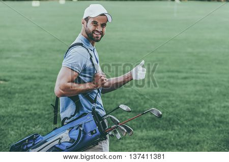 I love this game! Rear view of young happy golfer carrying golf bag with drivers and looking over shoulder while standing on golf course