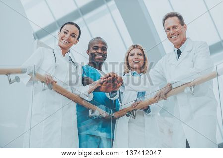 Confident medical experts. Low angle view of four happy medical doctors standing close to each other and holding their hands together while leaning at the handrail