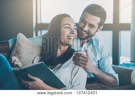 Spending nice time at home. Beautiful young loving couple bonding to each other and smiling while woman holding a book