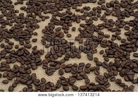 scattered grains of black coffee on canvas
