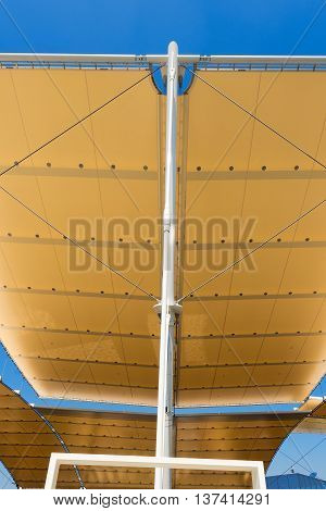 Detail of a modern tensile structure membrane fabric roof with poles and steel cables on a blue clear sky