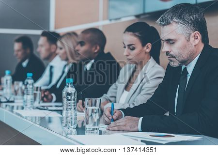 Business people on conference. Group of business people writing something in their note pads while sitting in a row