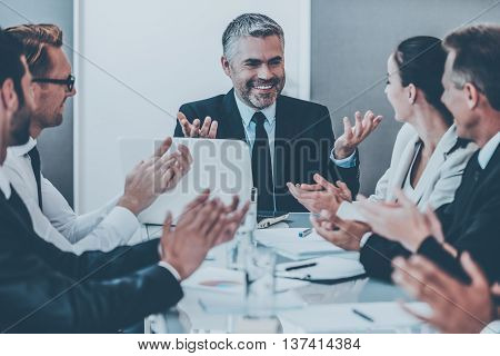 Great news! Confident mature man in formalwear smiling and gesturing while his colleagues applauding to him