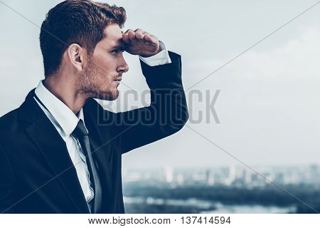 Looking for new opportunities. Thoughtful young man in formalwear holding hand on forehead and looking away while standing outdoors with cityscape in the background poster