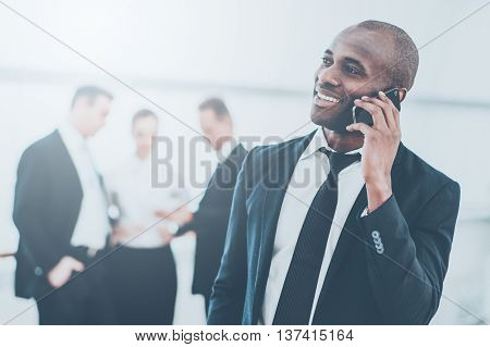 Sharing good news. Cheerful young African man in formalwear talking on the mobile phone and smiling while his colleagues standing on background