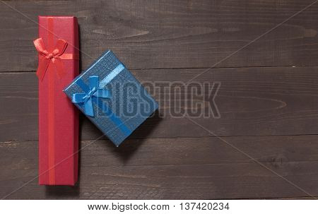 Red And Blue Gift Boxes Are On The Wooden Background With Empty Space