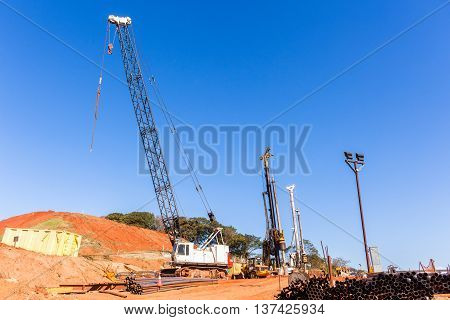 Construction industrial cranes for earthwork pylons installation for new road highway junction flyover ramps structures