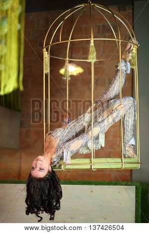 Beautiful woman in a shiny costume hanging in a golden cage