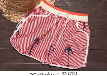 Swimming shorts and hat is on wooden background.