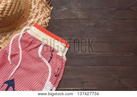 Swimming shorts and hat is on wooden background with copy space.
